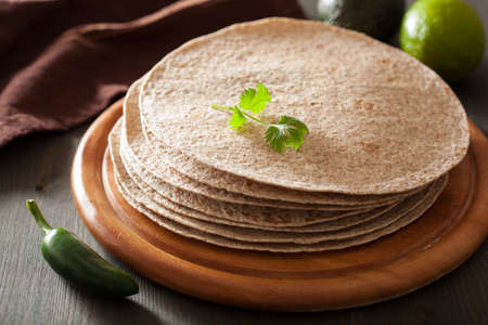 tortillas: whole wheat tortillas on wooden board and vegetables