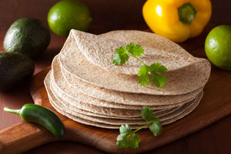 taco tortilla: whole wheat tortillas on wooden board and vegetables