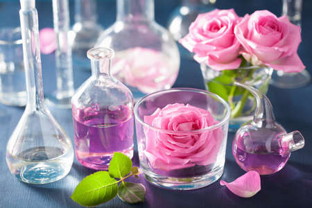 wooden aromatherapy: alchemy and aromatherapy set with rose flowers and chemical flasks Stock Photo