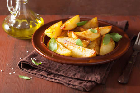wedges: baked potato wedges in plate over brown rustic table