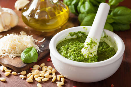 garlic: pesto sauce and ingredients over wooden rustic background Stock Photo