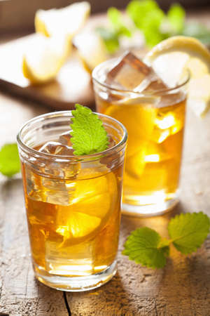 ice lemon tea: glass of ice tea with lemon and melissa