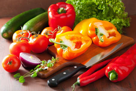 preparing food: chopping healthy vegetables pepper tomato salad onion chili on rustic background Stock Photo
