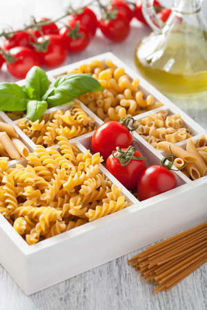 unboiled: various raw wholegrain pasta in white wooden box Stock Photo
