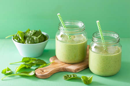 banana leaves: healthy green smoothie with spinach mango banana in glass jars Stock Photo