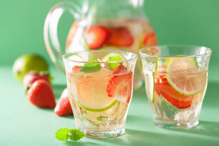 fresa: bebida de verano refrescante con fresa, pepino, limón en jarra y vasos Foto de archivo