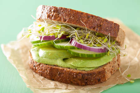 healthy rye sandwich with avocado, cucumber, alfalfa sprouts Imagens