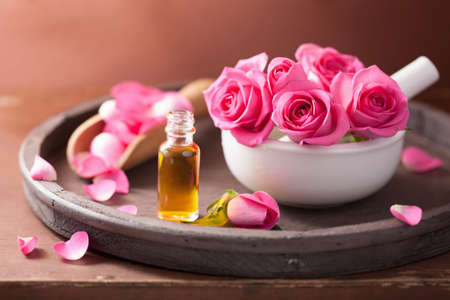 essential oil: spa set with rose flowers mortar and essential oil