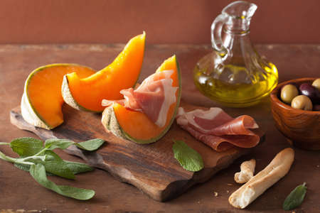 cantaloupe melon with prosciutto grissini olives. italian appetizer