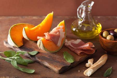 Melón con aceitunas grisines prosciutto. aperitivo italiano Foto de archivo - 41631779