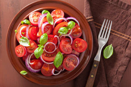 tomate ensalada: healthy tomato salad with onion basil olive oil and balsamic vinegar Foto de archivo