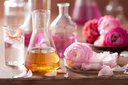 destilacion: alquimia y set de aromaterapia con flores ranúnculo y frascos Foto de archivo