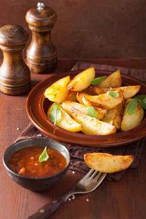 ovenbaked: baked potato wedges in plate over brown rustic table