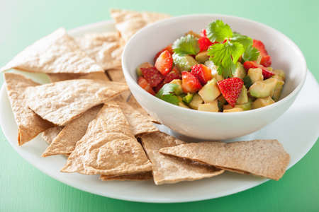 salad bowl: avocado strawberry salsa with tortilla chips Stock Photo