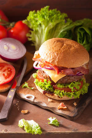 cooking bacon cheese burger with beef patty tomato onion