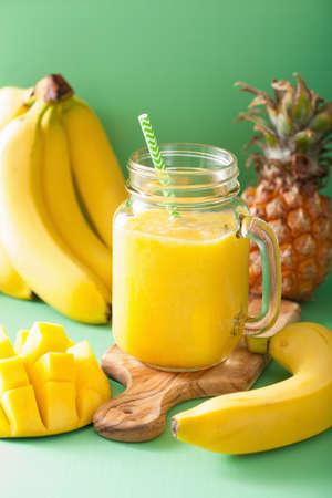mango fruta: smoothie amarillo sano con el pl�tano pi�a mango en tarros de cristal Foto de archivo