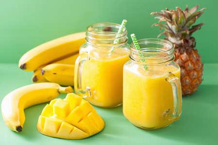 licuado de platano: smoothie amarillo sano con el plátano piña mango en tarros de cristal Foto de archivo