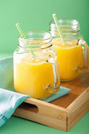 jugo verde: smoothie amarillo sano con el pl�tano pi�a mango en tarros de cristal Foto de archivo
