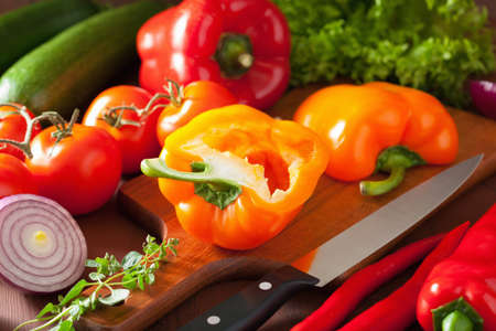knife tomato: chopping healthy vegetables pepper tomato salad onion chili on rustic background Stock Photo