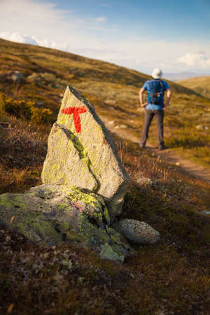 rout: T sign on rock and hiker with backpack traveling in Norway mountains Dovre