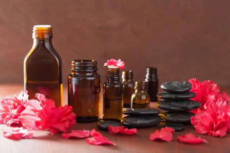 essential oil azalea flowers black massage stones Stock Photo