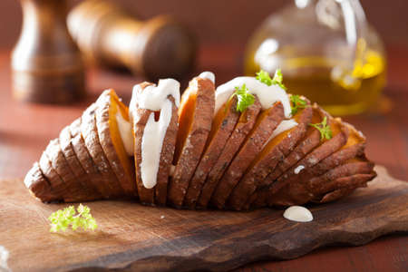 sour cream: Baked hasselback potatoes with sour cream Stock Photo