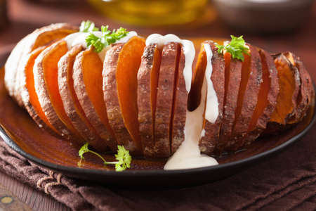 dinner jacket: Baked hasselback potatoes with sour cream Stock Photo