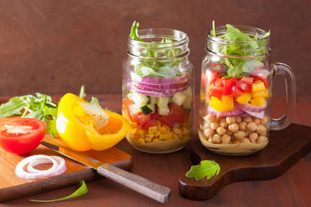 green herbs: healthy vegetable chickpea salad in mason jar