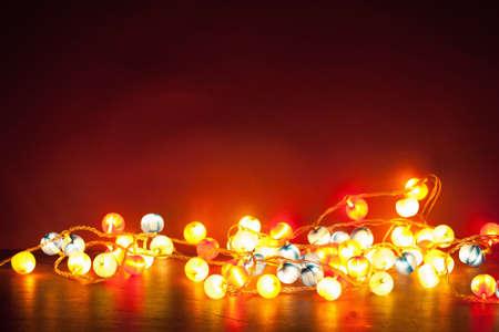 赤い背景の上のライトのクリスマスの装飾を燃焼