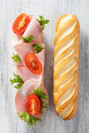long baguette sandwich with ham tomato lettuce Zdjęcie Seryjne