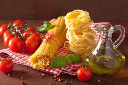 comida italiana: los tomates de aceite de oliva de pasta cruda. cocina italiana en la cocina rústica