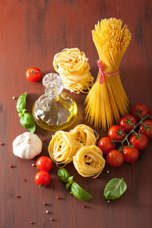 rustic kitchen: raw pasta olive oil tomatoes. italian cuisine in rustic kitchen Stock Photo