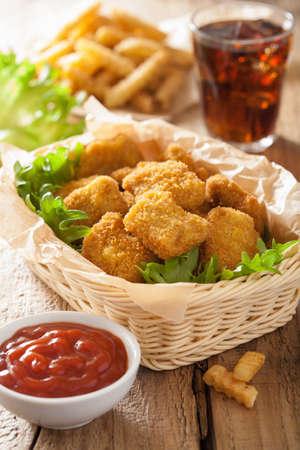 comida chatarra: nuggets de pollo de comida rápida con la salsa de tomate, papas fritas, refrescos de cola