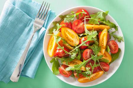 ensalada tomate: ensalada de tomate con rúcula sobre fondo verde Foto de archivo