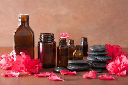 massieren: ätherisches Öl Azaleenblumen schwarze Massagesteine Lizenzfreie Bilder