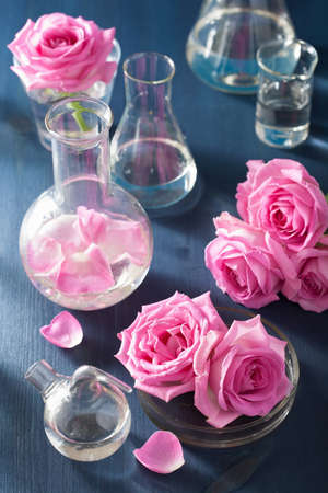 flasks: alchemy and aromatherapy set with rose flowers and chemical flasks Stock Photo