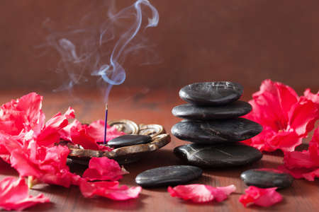 incense sticks for aromatherapy spa azalea flowers black massage stones spa Foto de archivo