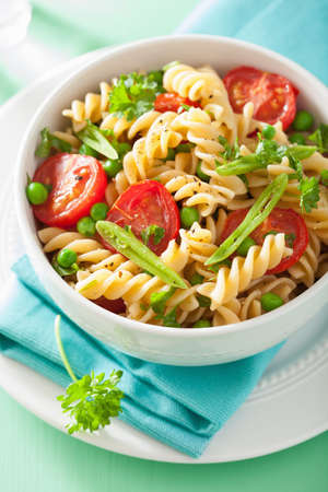 dish: vegetarian pasta fusilli with tomato peas herbs Stock Photo