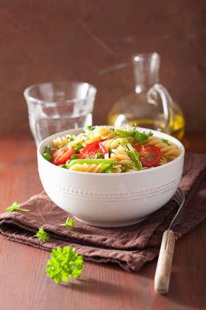 fusilli: vegetarian pasta fusilli with tomato peas herbs Stock Photo