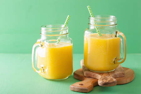 healthy mango pineapple smoothie in mason jars