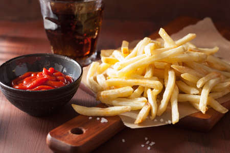 french fries with ketchup over rustic background Banco de Imagens