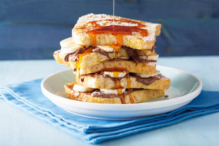 maple: pouring caramel over french toasts with banana chocolate sauce for breakfast