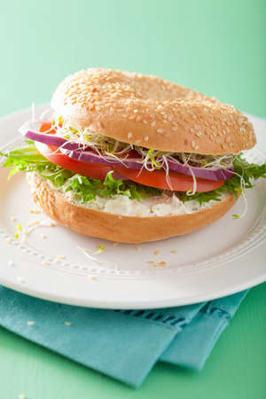 sprouts: tomato sandwich on bagel with cream cheese onion lettuce alfalfa sprouts