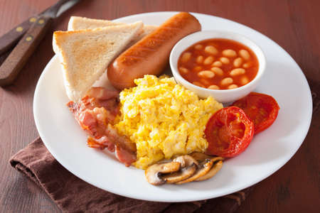 bacon and eggs: full english breakfast with scrambled eggs, bacon, sausage, beans, tomato Stock Photo