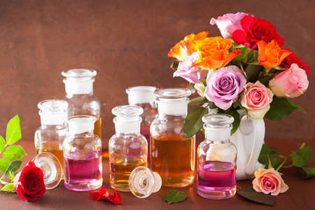 wooden aromatherapy: essential oil and rose flowers, aromatherapy spa perfumery Stock Photo
