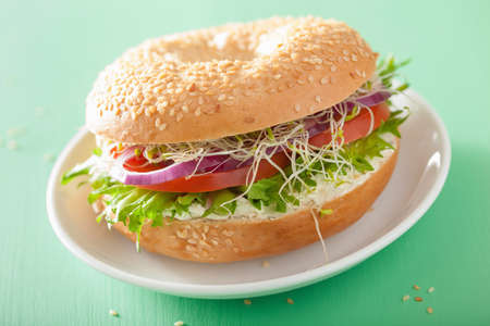 cream cheese: tomato sandwich on bagel with cream, cheese, onion, lettuce, alfalfa sprouts