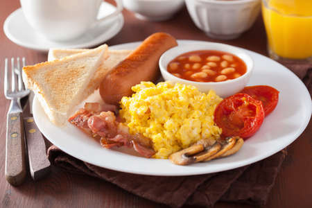 scrambled eggs: full english breakfast with scrambled eggs, bacon, sausage, beans, tomato Stock Photo