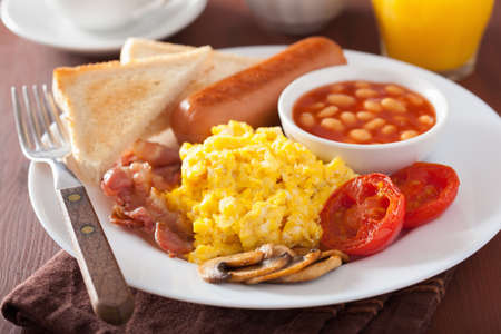 full english breakfast with scrambled eggs, bacon, sausage, beans, tomato Foto de archivo