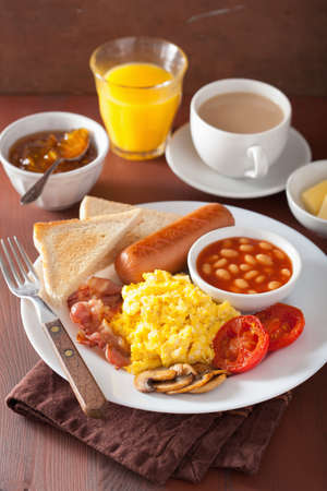 eggs and bacon: full english breakfast with scrambled eggs, bacon, sausage, beans, tomato Stock Photo
