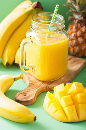 healthy yellow smoothie with mango pineapple banana in mason jars